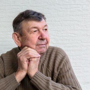 Portrait of elderly man, old senior crossed wrinkled hands