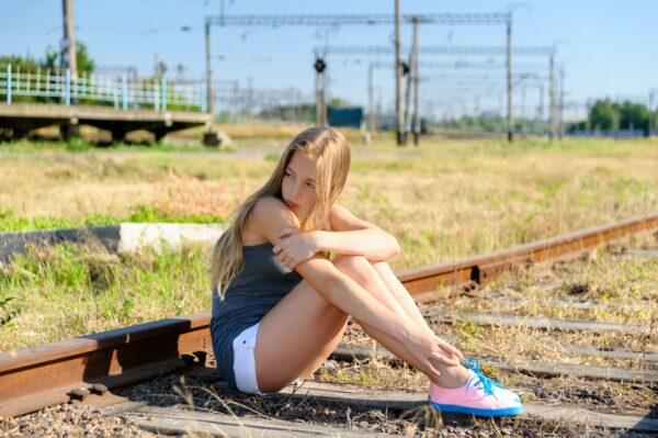 Sad young girl sitting lonely on rail track