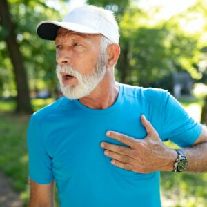 Senior man with chest pain suffering from heart attack during jogging
