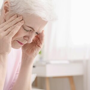 Senior woman having headache and touching her temples