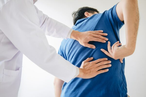 Doctor physiotherapist treating lower back pain patient after while giving exercising treatment on