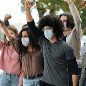 Students wearing protective face mask protesting and raising fists up