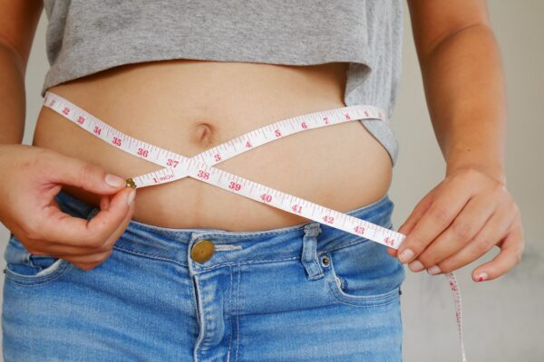 Woman measures her waist with overweight belly and abdomen.