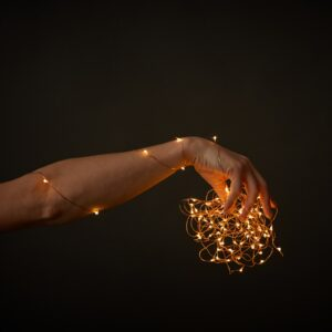 A woman's hand holds bright Christmas lights on a black background with space for text