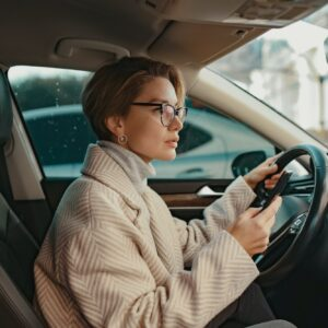 attractive stylish woman sitting in car dressed in coat