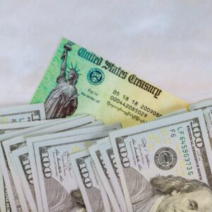Stimulus economic tax return check and USA currency hundred US dollar bills 1040 U