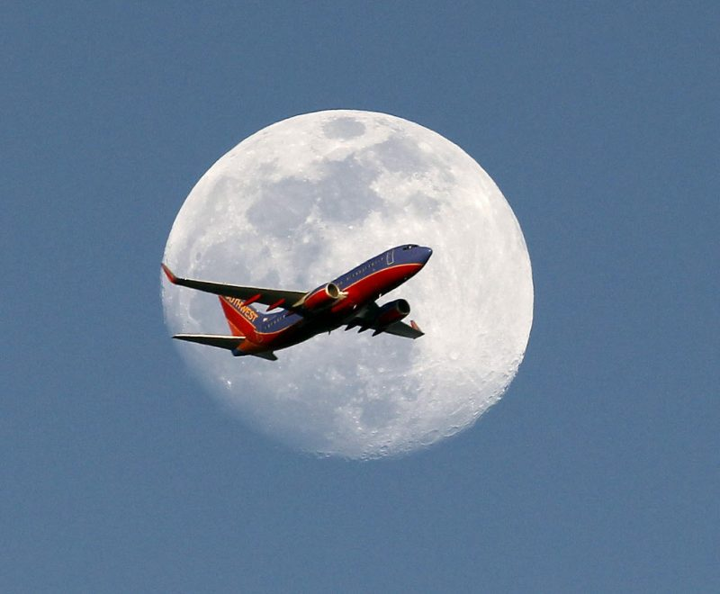 A Southwest Airlines passenger plane crosses the waxing gibbous moon in Whittier, Saturday, May 30, 2015. (AP Photo/Nick Ut)