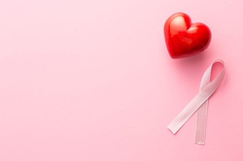 Pink breast cancer ribbon and heart on pink background.