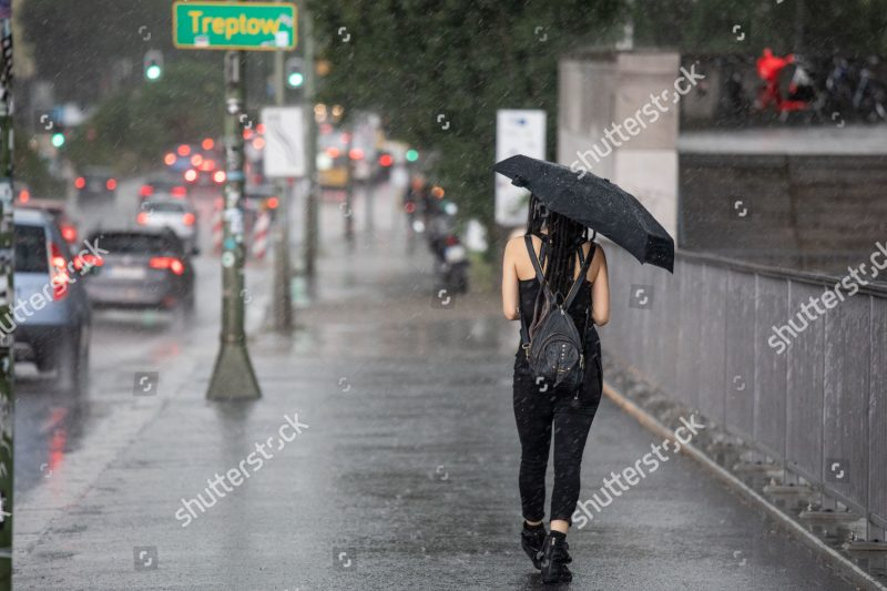 Mandatory Credit: Photo by OMER MESSINGER/EPA-EFE/Shutterstock (10352890k) A woman walks with an umbrella during heavy rain in Berlin, Germany, 02 August 2019. The German capital experienced heavy rains during afternoon hours. Heavy rain in Berlin, Germany - 02 Aug 2019