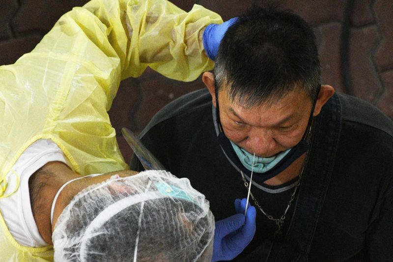 A healthcare worker collects swab samples for COVID-19 testing from a worker who is returning for work at a regional screening centre in Singapore (Xinhua/IANS)