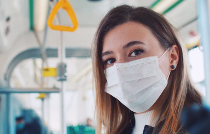Close up portrait of a young women wearing surgical mask.