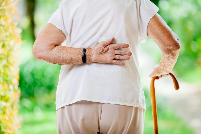 Elderly woman outdoors with back pain