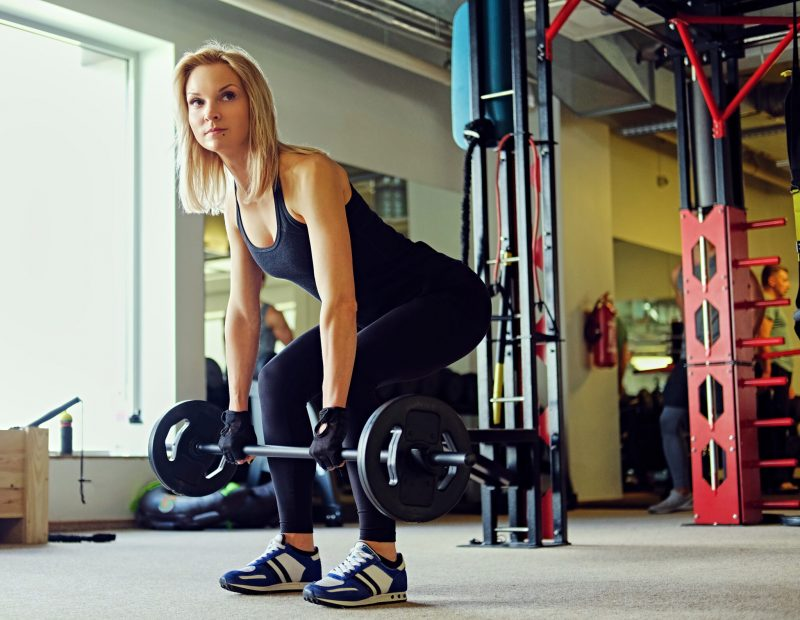 The full body image of blond sporty female holds barbell over TRX system on background in a gym club.