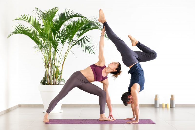 Two athletes performing duo acroyoga poses